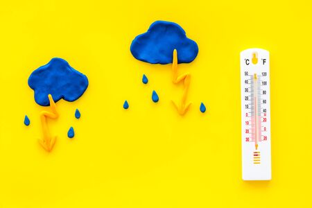 Rainy weather. Thermometer near clouds and drops on yellow background top view space for text
