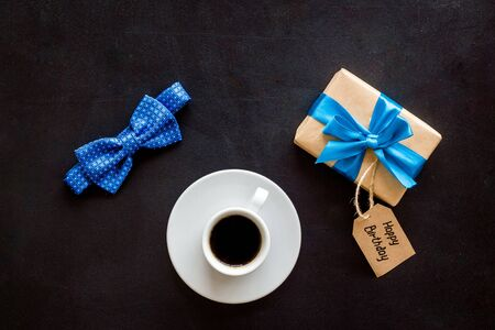 Mens birthday concept. Happy birthday text, present box, bow tie and coffee on black background top view f