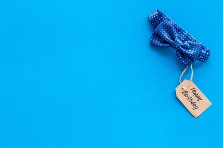 Mens birthday concept. Happy birthday text and bow tie on blue background top view copy space