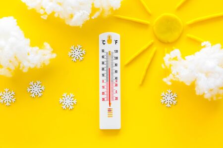Its snowing concept. Snow and thermometer on yellow background top view.