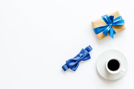 Greeting card for mens birthday. Present box, bow tie and coffee on white background top view frame space for text 스톡 콘텐츠