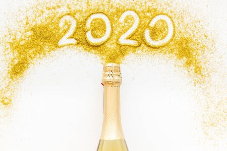 2020 Happy New Year concept. Date written on golden dust near champagne bottle on white background top view copy space