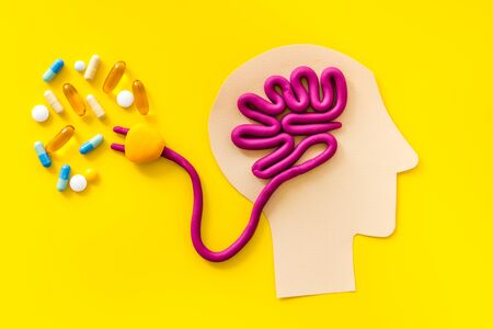 Brain charging and mental rest. Plug and cable leads to plastiline meanders on yellow background. Stock Photo
