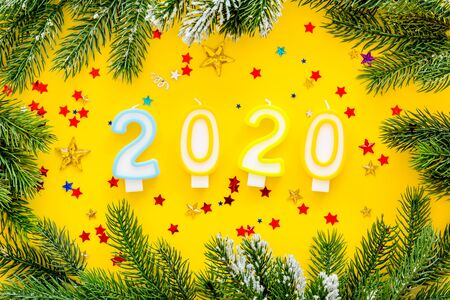 2020 New Year design. Date laid out by candles near fir branches on yellow background top view