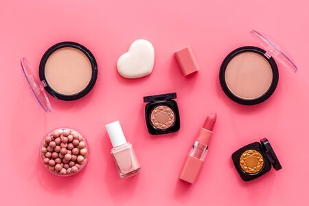 Makeup background with rounge, powder and tools on pink table top view