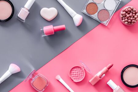 Decorative cosmetics frame on pink and grey background top view.