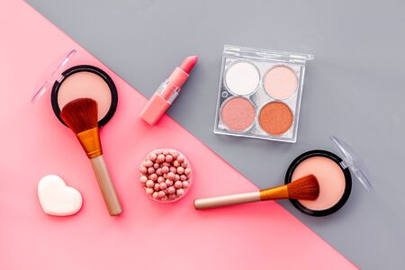 Makeup background with rounge, powder and tools on pink and grey table top view