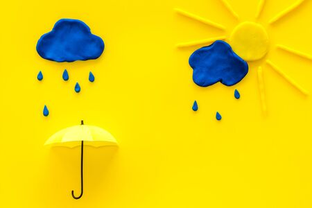 Weather forecast concept. Sunny and rainy. yellow background top view space for text Фото со стока