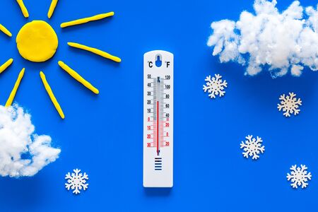 Its snowing concept. Snow and thermometer on blue background top view Stock Photo