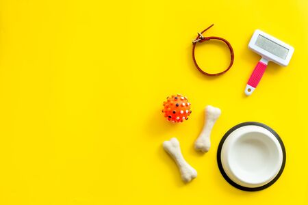 Set of treats and toys for pets with bones, collar and bowl on yellow background top view.
