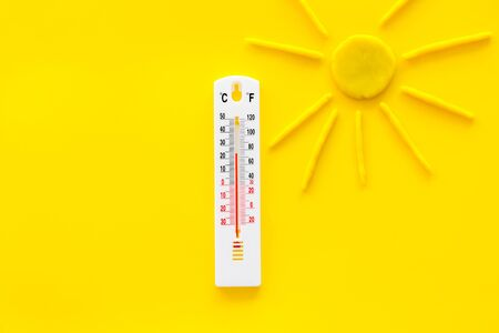 Sunny weather concept. Sun and thermometer on yellow background top view. 스톡 콘텐츠