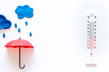 Rain concept. Weather thermometer near umbrella on white background top view space for text