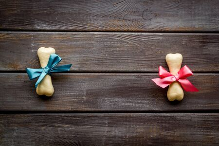 Small present for dogs. Chewing bones with bow on dark wooden background top view copy space