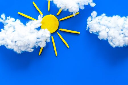 Cloudly weather concept. Sun and clouds on blue background top view space for text