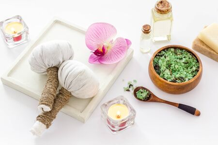Massage thai herbal balls near spa accessories and orchids on white background Stock Photo