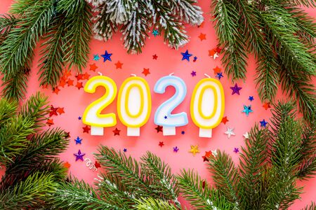 2020 New Year design. Date laid out by candles near fir branches on pink background top view 写真素材