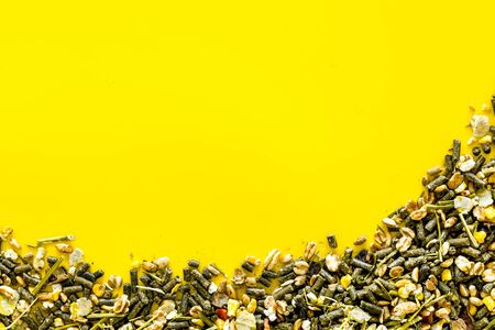 Pet food for rodents like rabbits, guinea pigs, hamsters on yellow background top view.
