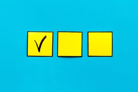 Check mark in check-box of check list on blue background top view.