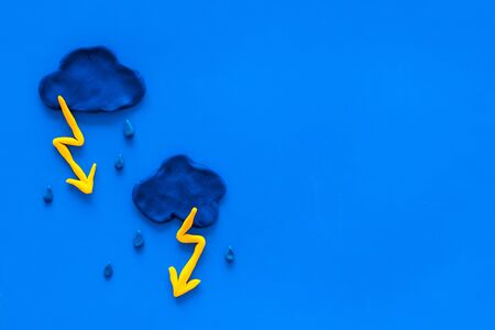 Storm concept, bad weather. Clouds and lightning on blue  top view copy space