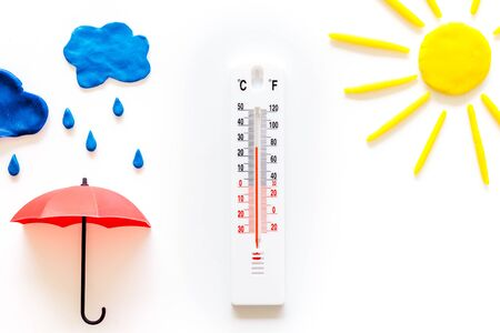Rain concept. Weather thermometer near umbrella on white top view copy space