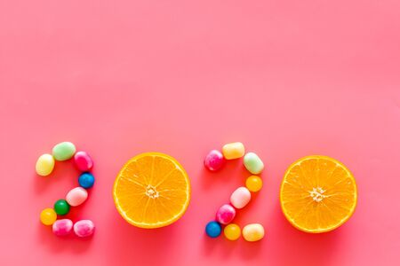 Sweet New Year design. 2020 laid out with candy and oranges on pink  top view copy space