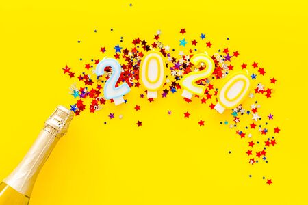 Celebrate New Year 2020. Candles on confetti near champagne bottle on yellow  top view copy space