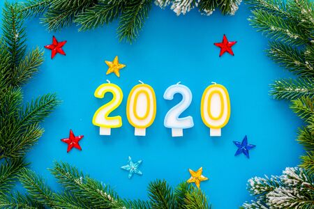 2020 New Year design. Date laid out by candles near fir branches on blue background top view. 写真素材