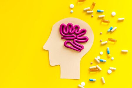 Treat brain diseases. Head with plastiline meanders and pills on yellow background top view.