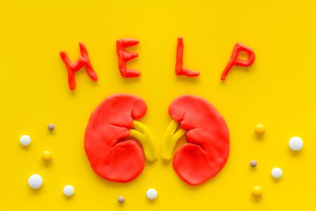 Kidney illness and treatment. Word help, organ, pills on yellow  top view