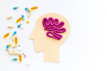Treat brain diseases. Head with plastiline meanders and pills on white background top view copy space