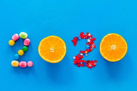 Sweet New Year design. 2020 laid out with candy and oranges on blue background top view. 写真素材