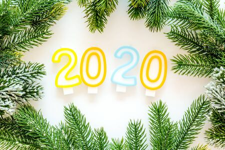2020 New Year design. Date laid out by candles near fir branches on white background top view