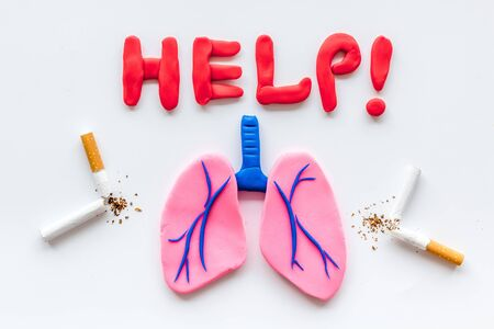 Harm of smoking and cancer. Word help, lungs and cigarettes on white  top view Stock Photo