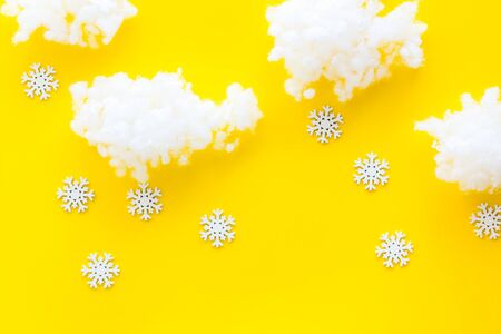 Its snowing concept. Snow on yellow background top view.