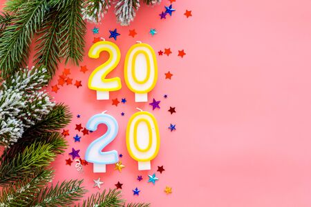 2020 New Year design. Date laid out by candles near fir branches on pink background top view copy space