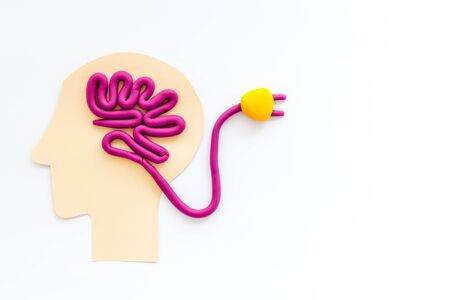 Brain charging and mental rest. Plug and cable leads to plastiline meanders on white background top view copy space
