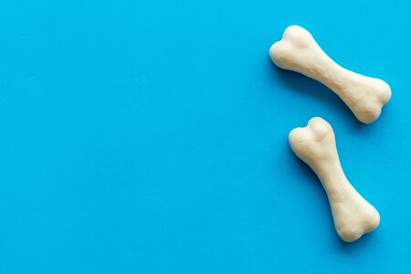 Treats for dogs. Chewing bones on blue background top view.