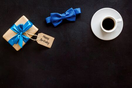 Mens birthday concept. Happy birthday text, present box, bow tie and coffee on black background top view.