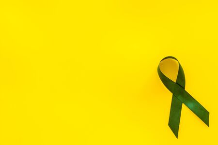 Green ribbon as symbol of disease control on yellow background top view space for text