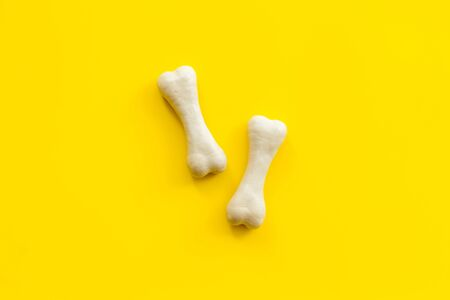 Food and toys for dogs. Chewing bones on yellow background top view. Фото со стока