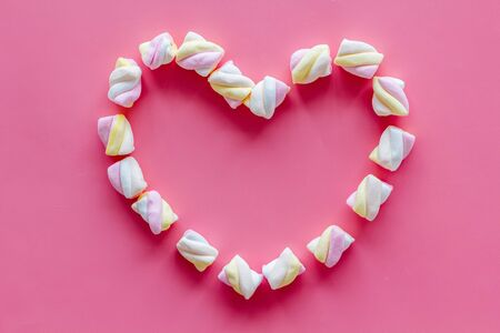 Pastel marshmallows background. Heart shaped set of sweets on pink table top view mockup copy space