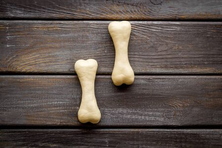 Food and toys for dogs. Chewing bones on dark wooden background top view copy space
