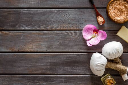 Massage table with thai herbal balls and orchids on dark wooden background top view frame space for text Stock Photo