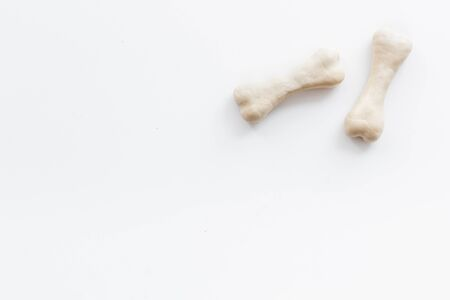 Treats for dogs. Chewing bones on white background top view space for text
