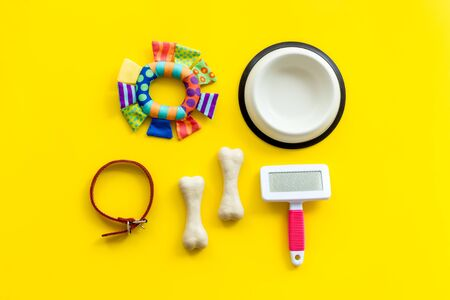 Pets accessories like bones, collar and bowl on yellow background top view. Фото со стока
