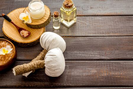Massage thai herbal balls near spa accessories on dark wooden background.