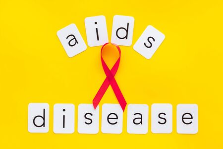 AIDS disease text near red ribbon on yellow background top view. 版權商用圖片