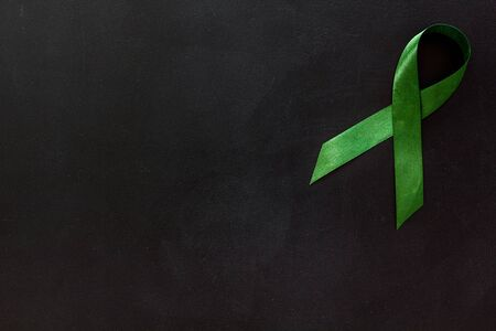 Green ribbon as symbol of disease control on white background top view space for text