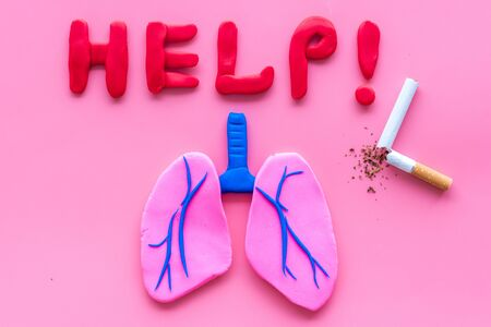 Harm of smoking and cancer. Word help, lungs and cigaretts on pink background top view