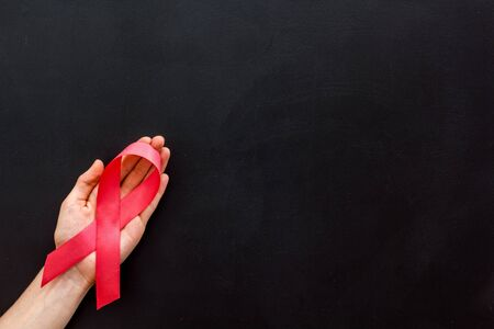 Pink ribbon in hands as symbol of breast cancer awareness on black background top view space for text